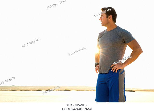 Man training, looking out from sunlit dry lake bed, El Mirage, California, USA
