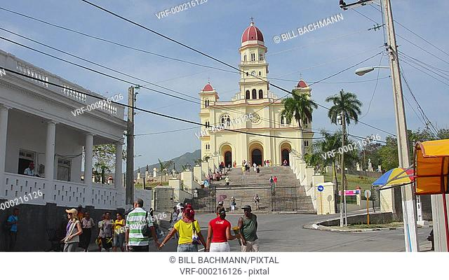 Santiago Cuba famous church called Basilica El Cobre containing the Virgin Mary medal with steeple and green grass on sunny day most important Cuban church