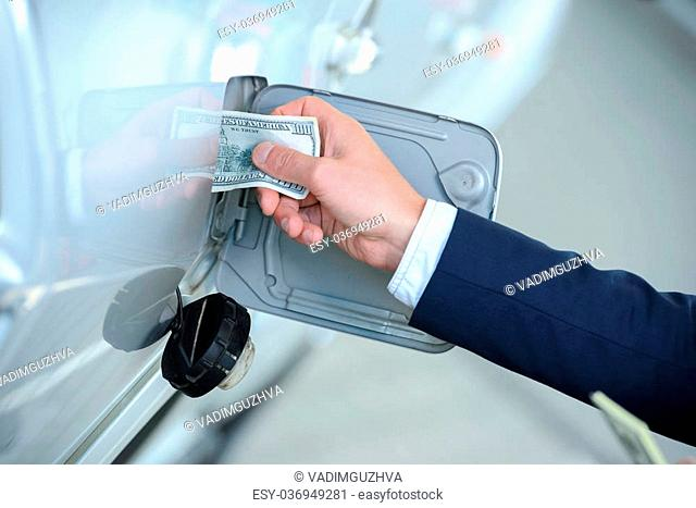 Hand of businessman that puts money into the tank of his car instead of gasoline at filling stations. Concept of expensive fuel