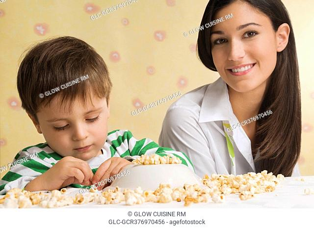Close-up of a boy sitting with his mother and playing with popcorn