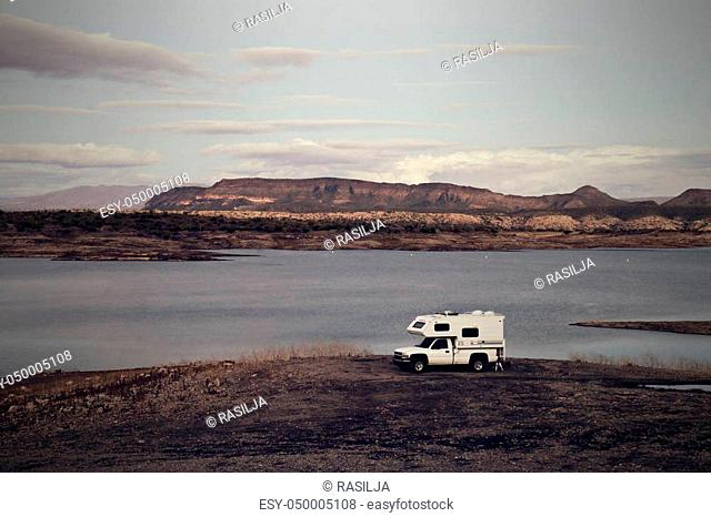 A travel camper is parked on the shoreline of Lake Pleasant, a reservoir near Phoenix, Arizona. Image processed with vintage effects