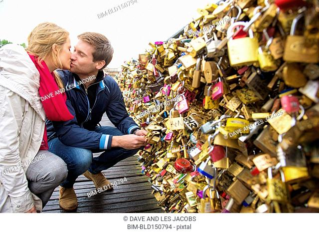 Kissing Caucasian couple locking padlock to bridge, Paris, France