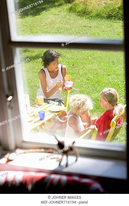 Family having breakfast in the garden, Sweden