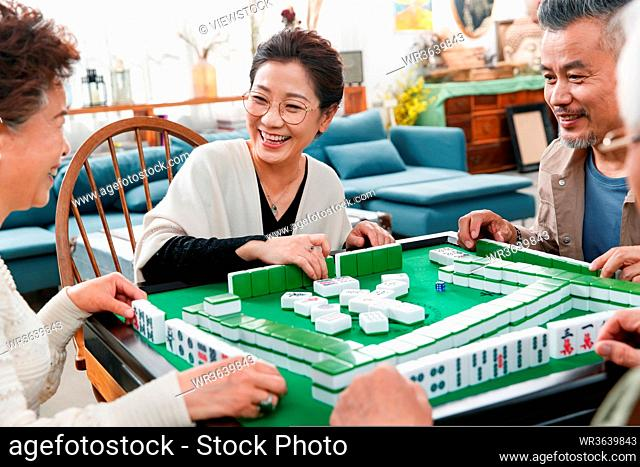 Happy old friends playing mahjong