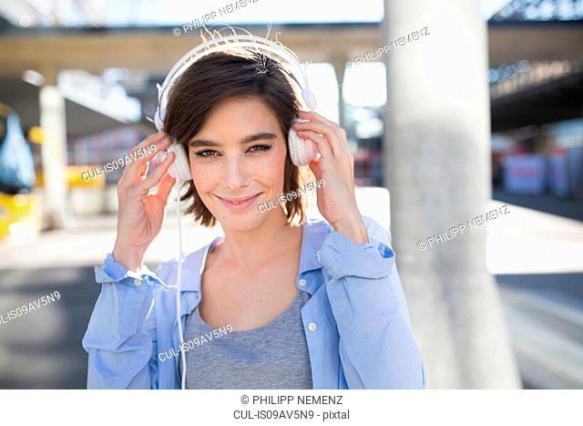 Portrait of mid adult woman adjusting headphones in city