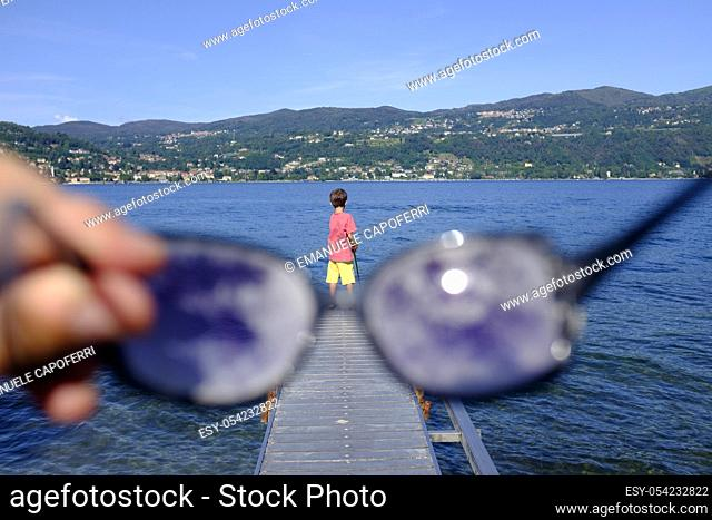 Watching child fishing from behind glasses, Lake Maggiore, Ranchi, Lombardy, Italy