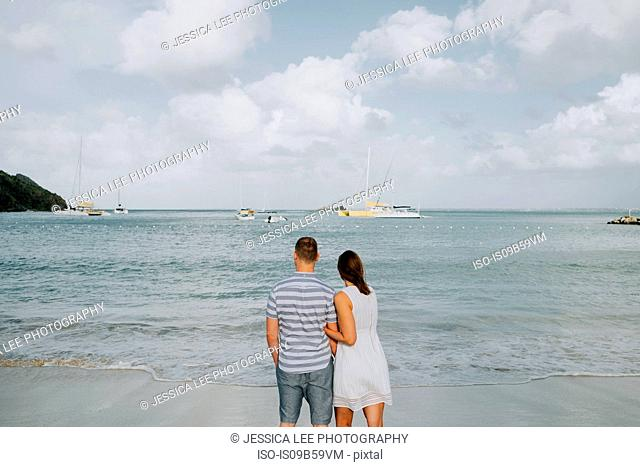 Couple standing, looking out to sea, rear view, Saint Martin, Caribbean
