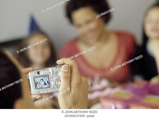 Father photographing family at birthday party