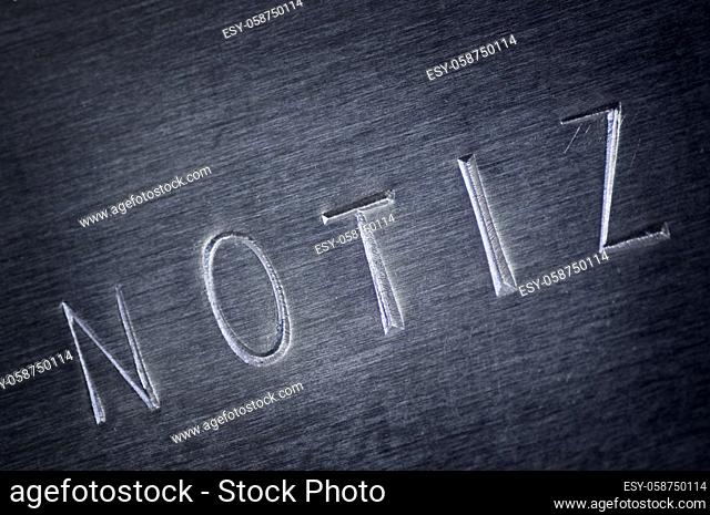 Close-up of a gray bevelled metal plate with the word NOTE stamped on it diagonally