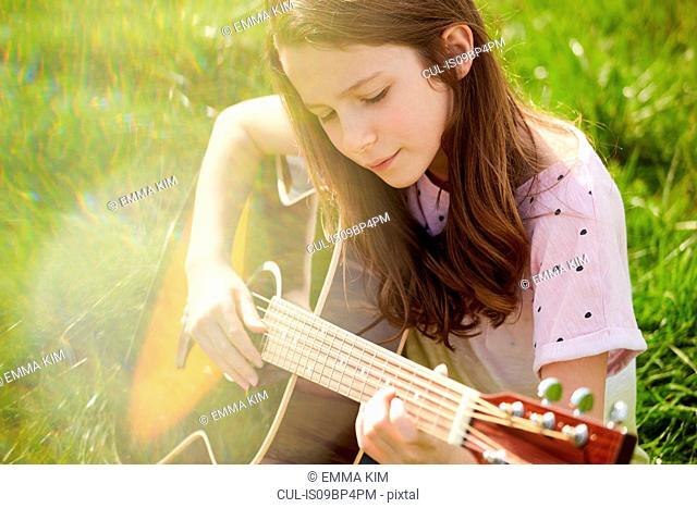 Girl playing guitar on grass