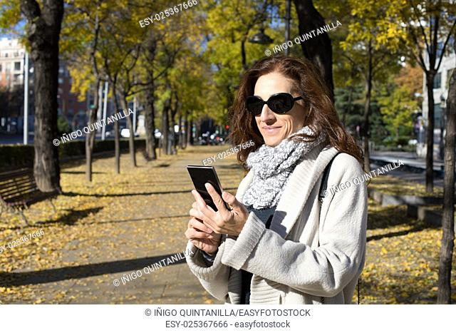 happy woman with grey cardigan and scarf, black sunglasses, watching smartphone in urban street in Madrid city with trees in autumn