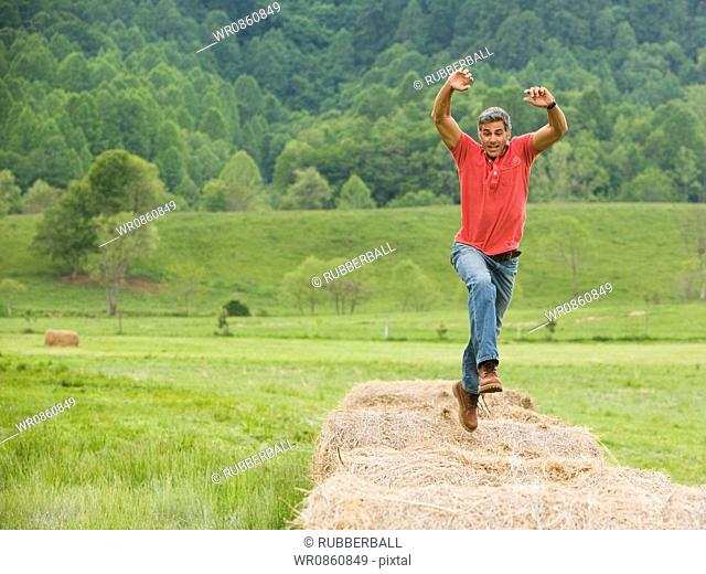 Portrait of a man jumping on a hay bale