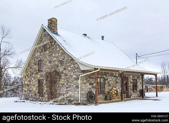 Old 1807 river and fieldstone cottage style house facade in winter, Quebec, Canada. This image is property released. CUPR0325