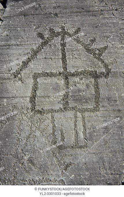 Petroglyph, rock carving, of a house on stilts. Carved by the ancient Camunni people in the iron age between 1000-1200 BC