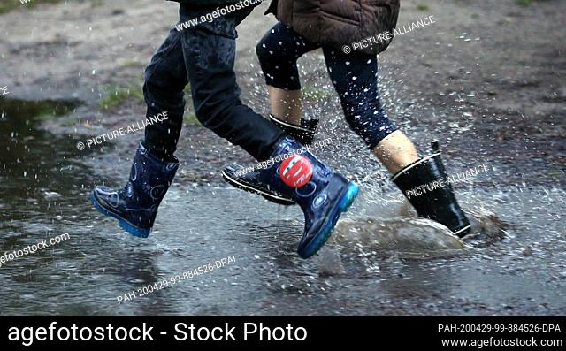 29 April 2020, Berlin: Children in the Köpenick district run with rubber boots through large rain puddles that have formed on the streets after heavy rain...