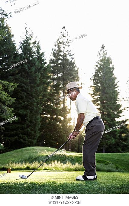 Senior golfer teeing off during a round of golf
