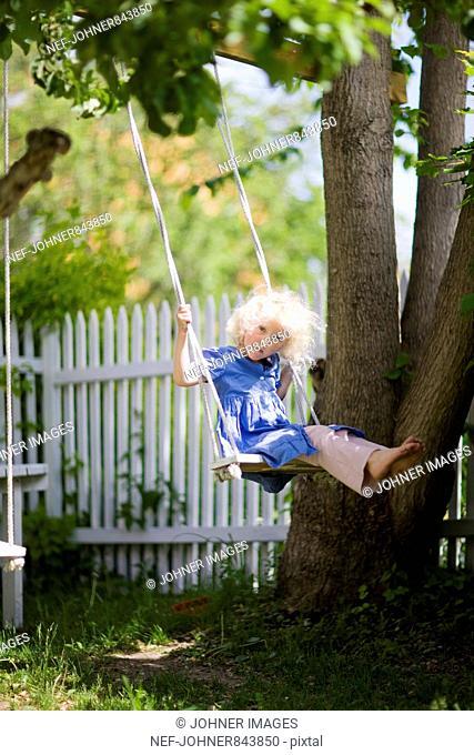 Girl on a swing in a garden, Sweden