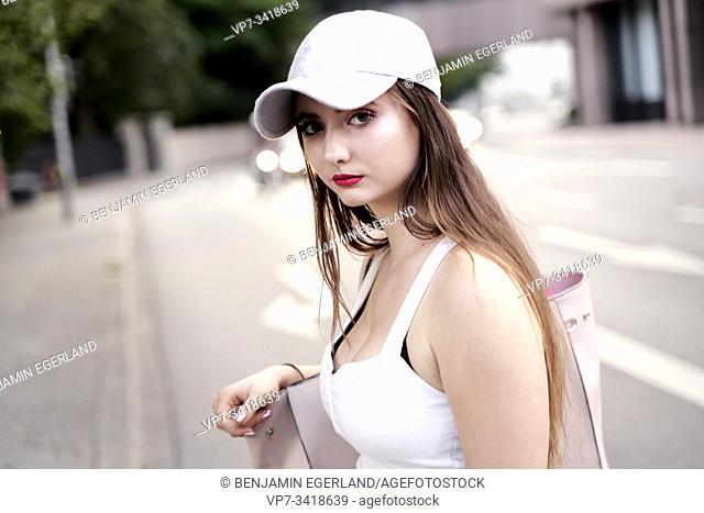 Young woman with baseball cap, looking at camera