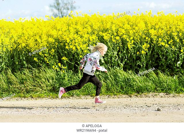 Profile view of girl running on dirt road at rapeseed field