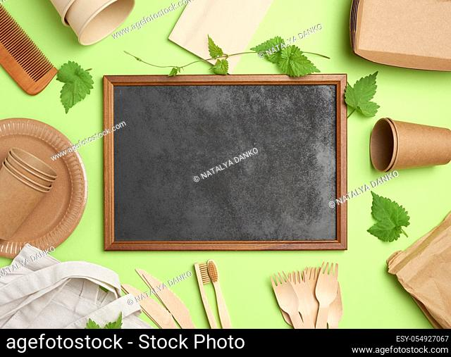 empty wooden frame and disposable paper plates, cups, wooden forks on green background. View from above, plastic rejection concept, zero waste