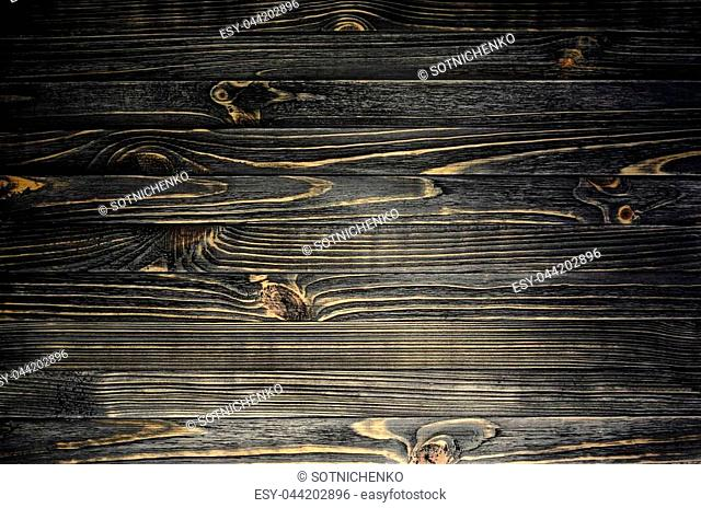 Black wood striped texture with vignette. A wooden surface lit by a spot of light