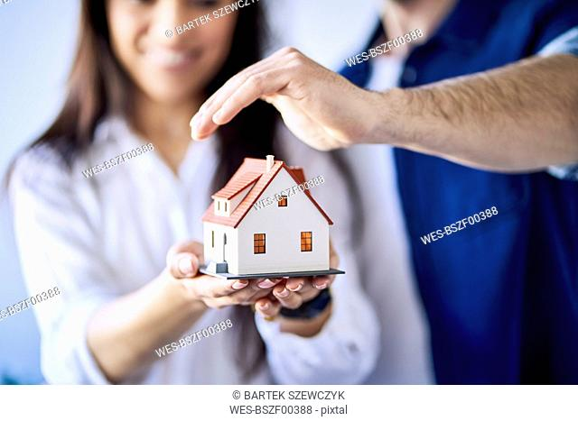 Close-up of couple holding model of new home