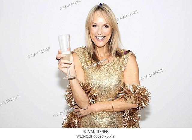 Senior woman wearing golden dress, celebtraing New Year's Eve