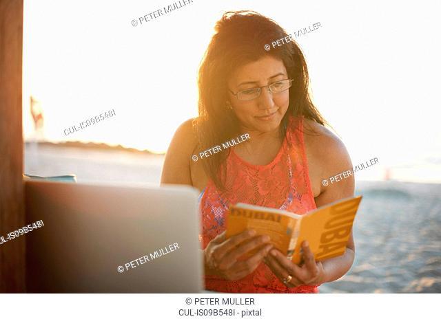 Mature woman on beach reading guide book, Dubai, United Arab Emirates