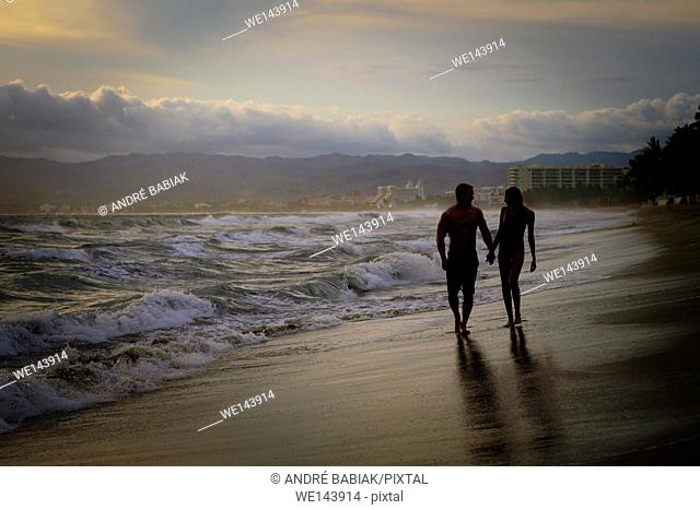 Silhouette of man and woman wlaking hand in hand at a beach at Riviera Nayarit, Mexico