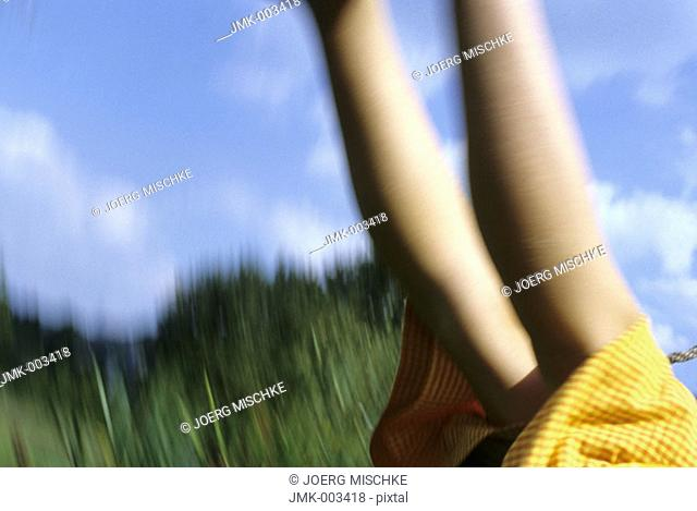 A girl, 5-10 years old, swinging outside in the garden in summer, blurred