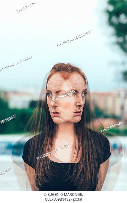 Double exposure portrait of young woman with freckles and long red hair