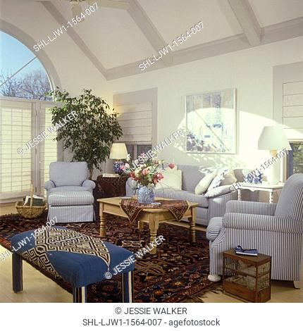 FAMILY ROOM: Light Country. Blue/white stripe ticking fabric on chairs and sofa, pine coffee table, floral arrangement, Kilim area rug and on table, birdcage
