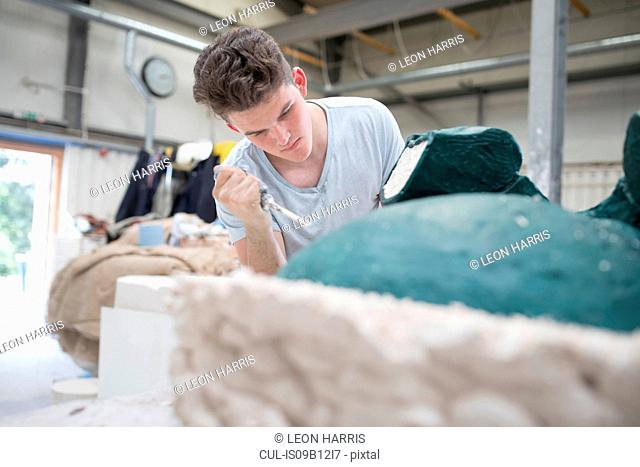 Young male foundry worker removing mould from bronze sculpture in bronze foundry