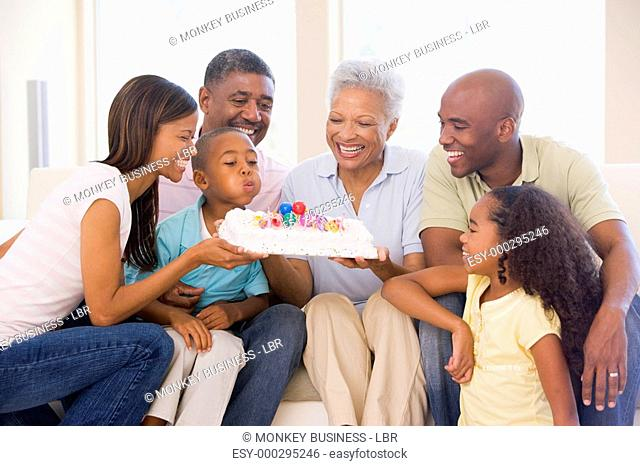 Family in living room smiling with young boy blowing out candles on cake