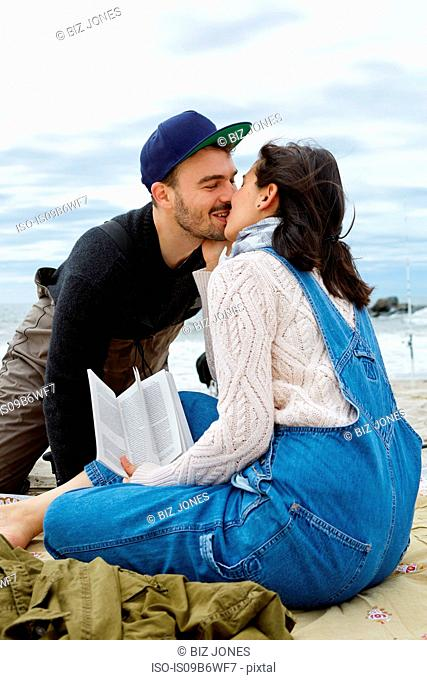 Young woman kissing sea fishing boyfriend on beach