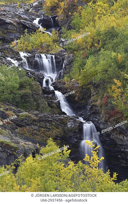 Autumn colours in Abisko national park Ridonjira waterfall. Lappland, Sweden