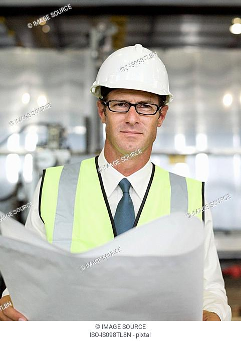 Mature man with blueprint in factory, portrait
