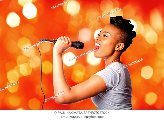 Beautiful teenager woman singing kareoke concert artist holding microphone, on red orange blurred lights background