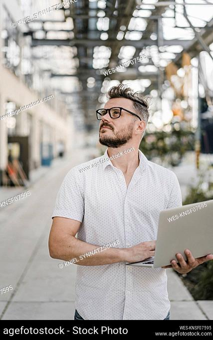 Young man holding laptop and looking up in the city