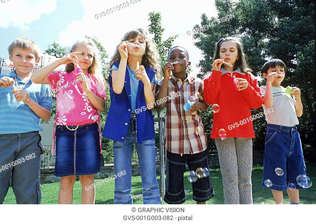 Young children blowing soap bubbles