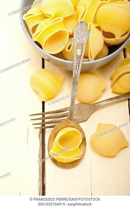 raw Italian snail lumaconi pasta on a blue bowl over rustic table macro