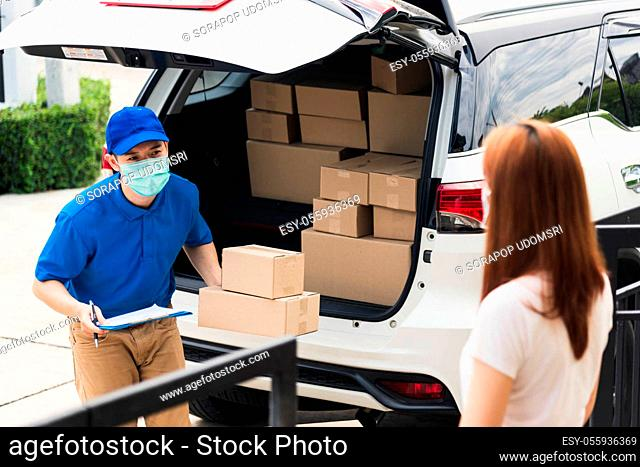 Asian young delivery man courier shopping online give parcel post box he protective face mask and service woman customer receiving boxed at front home door