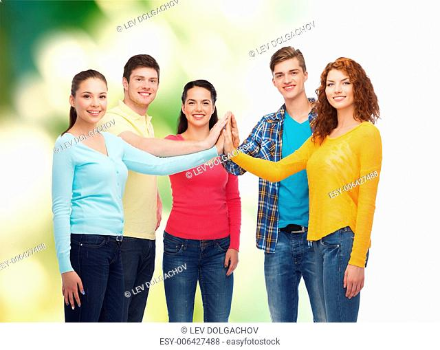 friendship, ecology, teamwork, gesture and people concept - group of smiling teenagers making high five over green background