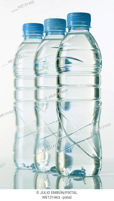bottles of mineral water on white base with bright background