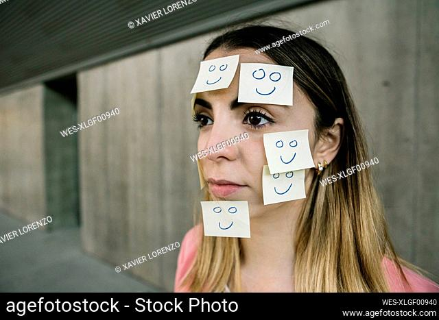Portrait of serious woman wearing adhesive notes on face