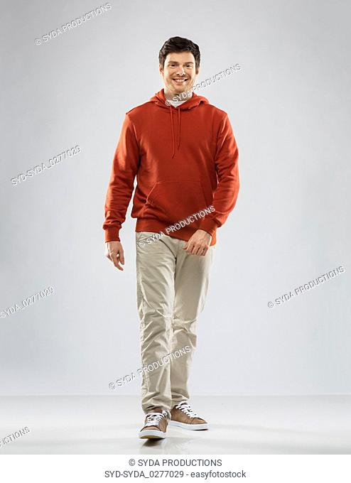 young man in red hoodie walking over grey