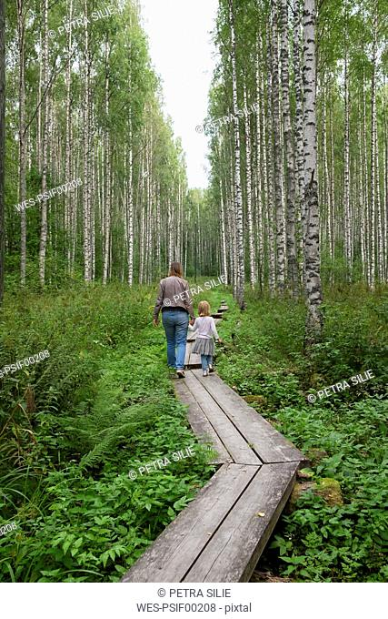 Finland, Kuopio, mother and daughter walking in a birch forest