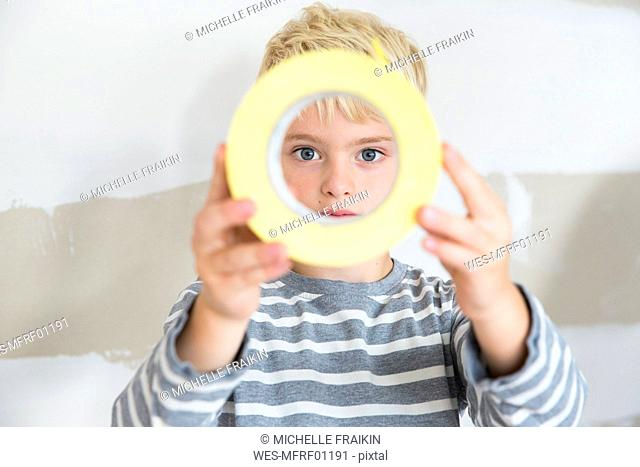 Portrait of boy looking through sticky tape toll