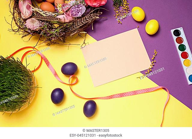 Easter card. Painted Easter eggs in nest on yellow table background. Top view of easter decoration. Happy easter concept. Trendy colors