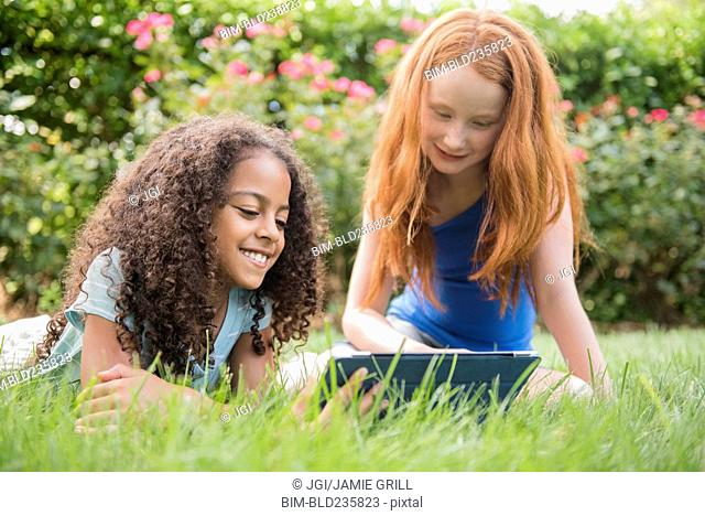 Smiling girls in grass field using digital tablet